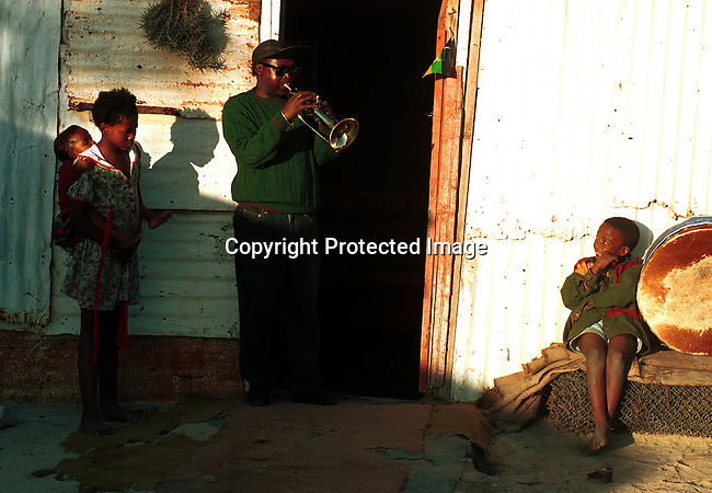 dimubus00024 Buskers. A jazz musician playing outside his schack in Guguletu, a poor township outside Cape Town, South Africa; election 1994; girl with baby on her back..©Per-Anders Pettersson/iAfrika Photos