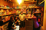 Small village shop lit up at night near Drugyel Dzong, Paro, Bhuthan...Bhutan the country that prides itself on the development of 'Gross National Happiness' rather than GNP. This attitude pervades education, government, proclamations by royalty and politicians alike, and in the daily life of Bhutanese people. Strong adherence and respect for a royal family and Buddhism, mean the people generally follow what they are told and taught. There are of course contradictions between the modern and tradional world more often seen in urban rather than rural contexts. Phallic images of huge penises adorn the traditional homes, surrounded by animal spirits; Gross National Penis. Slow development, and fending off the modern world, television only introduced ten years ago, the lack of intrusive tourism, as tourists need to pay a daily minimum entry of $250, ecotourism for the rich, leaves a relatively unworldly populace, but with very high literacy, good health service and payments to peasants to not kill wild animals, or misuse forest, enables sustainable development and protects the country's natural heritage. Whilst various hydro-electric schemes, cash crops including apples, pull in import revenue, and Bhutan is helped with aid from the international community. Its population is only a meagre 700,000. Indian and Nepalese workers carry out the menial road and construction work.