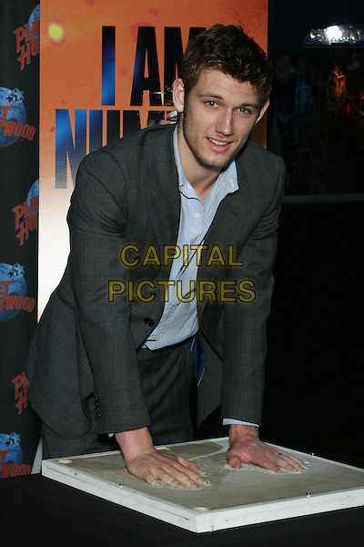 "ALEX PETTYFER.Alex Pettyfer at Planet Hollywood Times Square promoting his upcoming movie, ""I Am Number Four"", New York, NY, USA..February 7th, 2011.half length grey gray suit jacket blue shirt hands mould clay cement print leaning table stubble facial hair .CAP/LNC/TOM.©TOM/LNC/Capital Pictures."