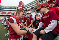 Hawgs Illustrated/BEN GOFF <br /> Bumper Pool, Arkansas linebacker, greets young fans Saturday, April 6, 2019, after the Arkansas Red-White game at Reynolds Razorback Stadium.