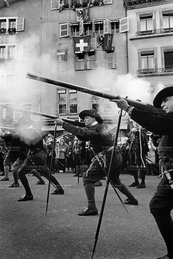 """Switzerland. Canton Geneva. Geneva. Old town. A group of men, all dressed with historic traditional soldiers outfits, are firing their arquebuses during the historical reenactment of  """"L'Escalade"""". The arquebus (sometimes spelled harquebus, harkbus or hackbut; meaning """"hook gun"""", or """"hook tube"""") is an early muzzle-loaded firearm used in the 15th to 17th centuries. An arquebus was originally a gonne with hook, and later a matchlock firearm. The matchlock was the first mechanism, or """"lock,"""" invented to facilitate the firing of a hand-held firearm. This design removed the need to lower by hand a lit match into the weapon's flash pan and made it possible to have both hands free to keep a firm grip on the weapon at the moment of firing, and, more importantly, to keep both eyes on the target. L'Escalade, or Fête de l'Escalade (from escalade, the act of scaling defensive walls), is an annual festival held in December in Geneva, Switzerland, celebrating the defeat of the surprise attack by troops sent by Charles Emmanuel I, Duke of Savoy during the night of 11–12 December 1602. The celebrations and other commemorative activities are usually held on 12 December or the closest weekend.<br /> 11.12.2016 © 2016 Didier Ruef"""