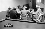 AZTEC, NEW MEXICO, USA  - JUNE 1971: MEN PLAYING DOMINOES IN BAR WITH POOL TABLE.   Six 6 middle old age retired seniors OAP  men male in  pool hall playing dominoes talking passing the time of day concentration wearing cowboy hats candid reportage interior scene .