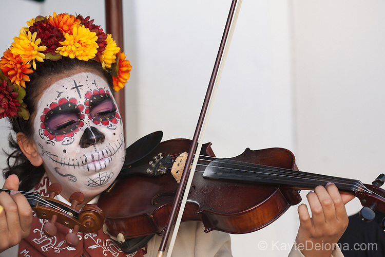 Mexican woman with calavera face paint plays mariachi violin at the Day of the Dead celebration at the Bowers Museum in Santa Ana, CA