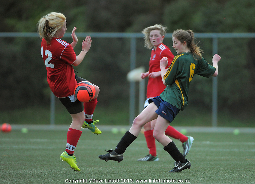 Action from Wellington girls college football bronze playoff final between Sacred Heart College (red) and Wellington High School at Wakefield Artificial Turf,  Wellington, New Zealand on Wednesday, 21 August 2013. Photo: Dave Lintott / lintottphoto.co.nz