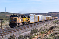 Union Pacific 5557, a model GP50, pulls a train of auto transports west out of Evanston, Wyoming, towards Utah.