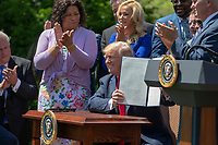 """United States President Donald J. Trump holds up a signed Executive Order """"to ensure that all faith-based communities have strong advocates in the White House"""" during a National Day of Prayer event in the Rose Garden at the White House in Washington, DC on May 3, 2018. Credit: Alex Edelman / CNP /MediaPunch"""