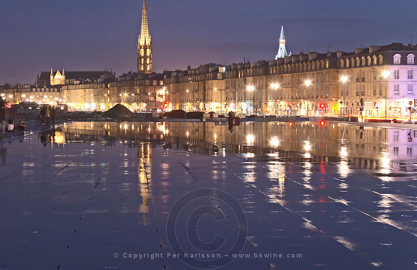 Tower and church Eglise Saint Michel. On Les Quais. Place de la Bourse. The new fountain Miroir d'Eau, Water Mirror, making reflections. Bordeaux city, Aquitaine, Gironde, France