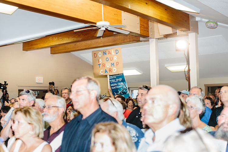 """A sign reading """"Donald Trump is Our Trump Card"""" rises above a crowd of supporters as real estate mogul and Republican presidential candidate Donald Trump speaks at a rally at the Weirs Beach Community Center in Laconia, New Hampshire."""