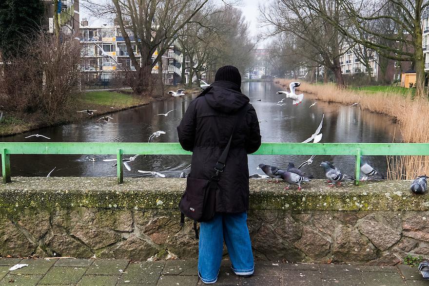 Nederland, Amsterdam, 13 feb 2015<br /> Vouw voert de eendjes en andere vogels met oud brood. Door te veel voeren komen er ook te veel muizen en ratten in de stad.<br /> Foto: (c) Michiel Wijnbergh