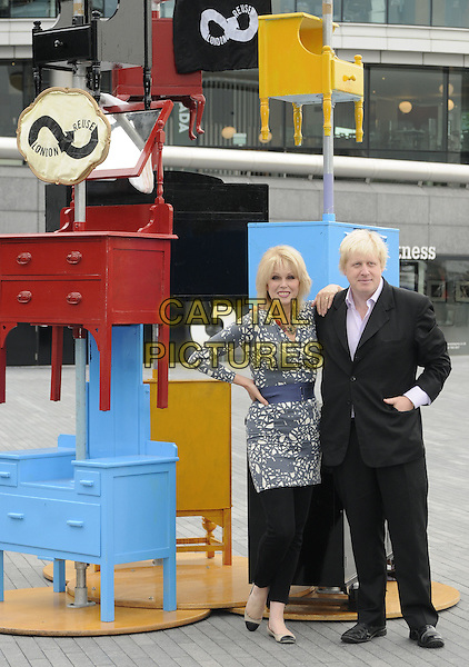 JOANNA LUMLEY & BORIS JOHNSON (Mayor of London).The launch of the old furniture recycling scheme, The Scoop, More London, the Queen's Walk, London, England..July 12th, 2010.full length black suit grey gray white print top blue waist belt trousers leggings leaning on shoulder hand in pocket on hip dresser chest of drawers.CAP/CAN.©Can Nguyen/Capital Pictures.