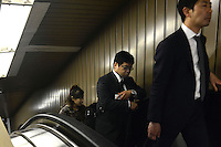 Businessmen on an escalator on the Tokyo underground, Tokyo, Japan.<br /> April-2014