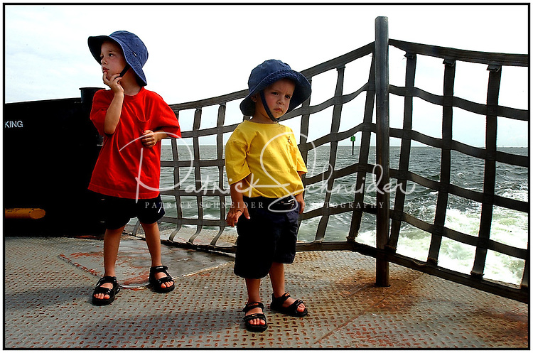 Two boys stand aboard a ferry taking their family's vehicle over to Ocracoke, N.C. in the North Carolina Outer Banks. Image is model released and can be used to illustrate other locations.