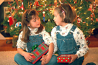 Sisters age 8 and 6 opening Christmas presents by tree.  St Paul  Minnesota USA
