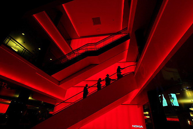 People on an escalator are silhouetted against a backdrop of red during the opening night at the Nokia Theater in downtown Los Angeles Thursday October 17, 2007.