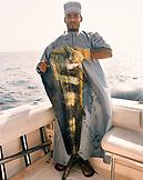 OMAN, fisherman holding mahi mahi fish, portrait