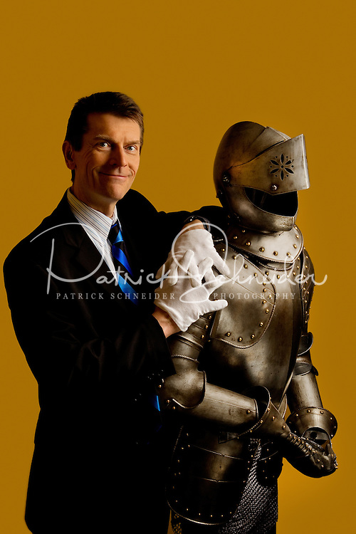 Portrait photography of Michael Eury, Executive Director of the Concord Museum, shown here with one of the Concord Museums most popular attractions, a replica suit of armor. The replica, approximately 200 years old and of European origin, hailed from the collection of E. T. Cannon, one of Cannon Mills founder J. W. Cannons six sons. Mr. Cannon donated the armor in the early 1940s to Memorial Hall, the Concord Museums original name. Photo is part of a photographic series of images featuring Concord, NC, by Charlotte-based photographer Patrick Schneider..