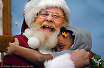 Santa, aka Harry Miller, gives and receives a hug from Delana Wagner at the Head Start at French Villas in St Petersburg.