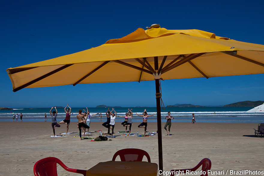 Young people practicing yoga at Geriba beach, Armacao de Buzios, Rio de Janeiro State, Brazil.  Physical, mental, and spiritual practice with a view to attain a state of peace and wellness.