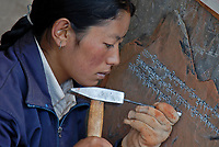 A Tibetan girl carving Mani stone plates, rocks and/or pebbles, inscribed with the six syllabled mantra Creating and carving mani stones as devotional or intentional process art under the influence of Tibetan Buddhism. The mantra of Avalokiteshvara is also a common design on prayer wheels