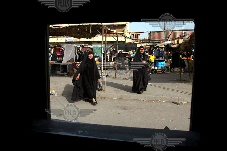 A US army Humvee patrol passes Iraqi women in a Sadr City market.