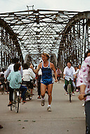 Danang, February 1988. Crossing the Perfume River and old French built bridge link the two sides of the city. There is an endless traffic on that bridge. Here an American, Coterel, who has already crossed America, Europe and China, running, crossing Vietnam from North to South.