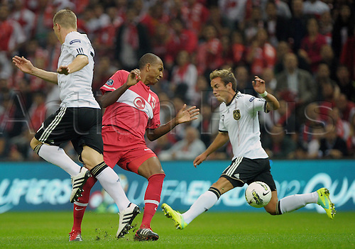 07.10.2011 Istanbul Turkey.  Germany's Mario Goetze (R)and BastianSchweinsteiger (L) vie with Mehmet Aurelio of Turkey's during the EURO 2012 qualifying match between Turkey and Germany at the Turk Telekom Arena.
