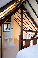 A guest bedroom has been tucked under the eaves with a view of the stars from a large skylight situated over the antique bedstead