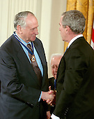 "Washington, D.C. - December 15, 2006 -- William Safire receives the Presidential Medal of Freedom  from United States President George W. Bush and first lady Laura Bush during a ceremony in the East Room of the White House on Friday, December 15, 2006.  The medal is the nation's highest civil award.  It may be awarded ""to any person who has made an especially meritorious contribution to (1) the security or national interests of the United States, or, (2) world peace, or (3) cultural or other significant public or private endeavors"".  As a journalist, speechwriter, columnist, author, and lexicographer, William Safire has distinguished himself as one of our country's most talented writers and commentators.  Using the power of prose, he has educated our citizenry, polished our language, and vigorously defended human freedom.  His work has earned him the recognition of his peers, including the Pulitzer Prize for Distinguished Commentary, and has elevated debate on issues of the day.  The United States honors William Safire for his uncompromising commitment to his craft and to strengthening our democracy.<br /> Credit: Ron Sachs / CNP"
