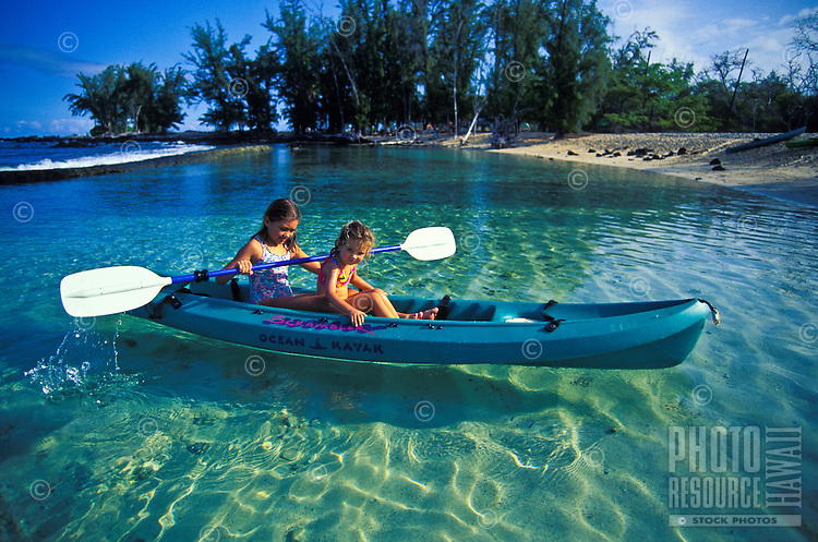 Young girls kayak at Makalawena Beach, Kona Coast, Big Island of Hawaii