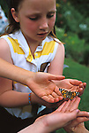 Children releasing a butterfly in a garden