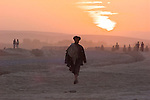 An Afghan man walks at sunset through the town of Dasht-e-Kala