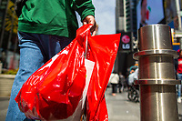 NEW YORK, NY - APRIL 2: A man carries his shopping  plastic bag as he walks along Times Square on April 2, 2019 in New York. New York will become the second state in U.S. to ban shops from providing single-use plastic bags for most purchases.   (Photo by Eduardo MunozAlvarez/VIEWpress)