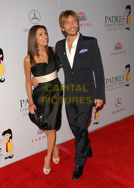 EVA LONGORIA & KEN PAVES.The 7th Annual El Sueno de Esperanza Benefit Gala to raise funds for Padres Contra El Cancer held at The Lot in West Hollywood, California, USA..October 18th, 2007.full length black dress cream sash waist arm around waist clutch purse grey gray suit shoes platform .CAP/DVS.©Debbie VanStory/Capital Pictures