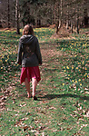 A913GB Young girl walking in daffodil woods in springtime
