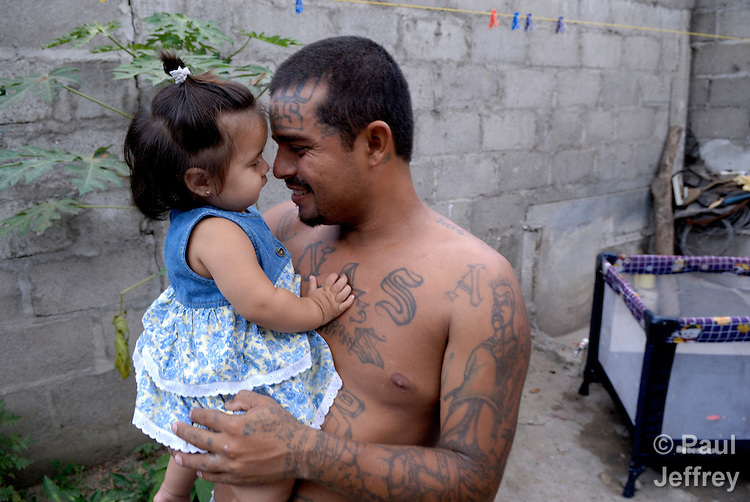 Henri Aguilar with his one-year old daughter Genesis in the yard of their home. This photo was captured May 2, 2007. On May 7, 2007, he was assassinated by three masked men. Aguilar was a former member of the Mara Salvatrucha, but under the guidance of a Catholic program had left the gang and was married, working full time, and heavily involved in parish life.