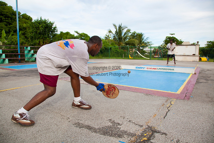 "Originating in Barbados in the 1930s, Road Tennis is played in on the back streets and roads of the country or now in permanent courts, such as the ones in Oistins and Speightstown.  The game is played on a 10x20 foot court and the ""net"" is an 8 inch by 10 foot piece of wood.  It has the same rules as table tennis (ping pong) and is a 21 point game.  It uses hand hewn rackets made largely from plywood and tennis balls that have had the fur removed.  It is the only endemic sport to Barbados and is wildly popular among the local population.  Pictured here are the road tennis courts at the Bush Hall Community Center.  An old windmill sits on the property."
