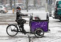 Vrouw fietst met bakfiets in een sneeuwstorm