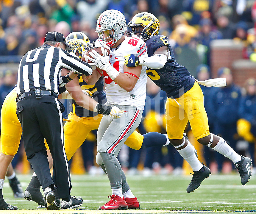 A referee gets tangled up as Ohio State Buckeyes tight end Nick Vannett (81) makes a reception at Michigan Stadium on November 28, 2015. (Chris Russell/Dispatch Photo)
