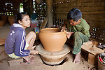 Man Making Pottery Wiht Daughter Spining Wheel
