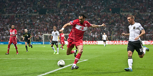 07.10.2011 Istanbul Turkey.  Germany's Lukas Podolski (R) and Turkey`s Servet Cetin (L) vie for the ball during the EURO 2012 qualifying match between Turkey and Germany at the Turk Telekom Arena.