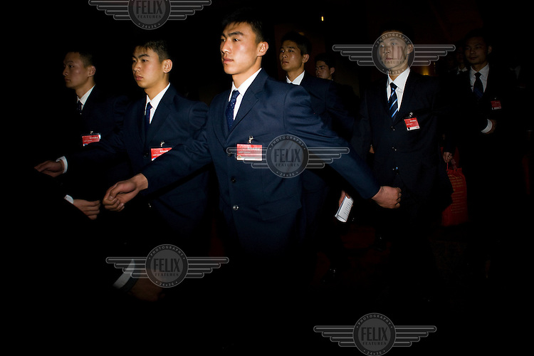 Security guards march through the Great Hall of the People after the Chinese People's Political Consultative Conference (CPPCC), plenary session for the NPC (National People's Congress).