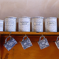Blue and white mugs hang beneath a shelf of old-fashioned enamel canisters