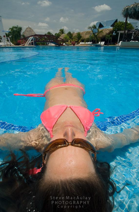 Young woman in pink bikini floating on back at the side of swimming pool, Playa Blanca Resort, Panama.