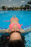 Young woman in pink bikini floating on back at the side of swimming pool, Playa Blanca Resort, Panama.