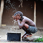 """Gota Dzongololo, 11, washes his face in the morning before getting dressed to go to school. He lives in Chidyamanga, a village in southern Malawi that has been hard hit by drought in recent years, leading to chronic food insecurity, especially during the """"hunger season,"""" when farmers are waiting for the harvest."""