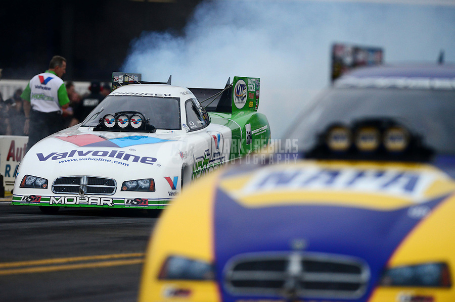 Nov. 8, 2012; Pomona, CA, USA: NHRA funny car driver Jeck Beckman (left) does a burnout alongside teammate Ron Capps during qualifying for the Auto Club Finals at at Auto Club Raceway at Pomona. Mandatory Credit: Mark J. Rebilas-
