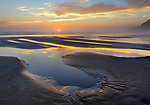 Tillamook County, Oregon: Sunset and clouds reflected in tide pools at low tide