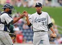 Pitcher Jorge DeLeon (32) of the Lexington Legends high-fives his catcher, Roberto Pena (10) after closing out a win against the Greenville Drive on June 5, 2011, at Fluor Field at the West End in Greenville, S.C. Photo by Tom Priddy / Four Seam Images