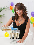 USA, Illinois, Metamora, Woman pouring champagne into flutes at party