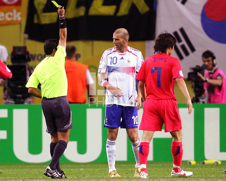 Referee Benito Archundia gives a yellow to Zinedine Zidane (10) of France. The Korea Republic and France played to a 1-1 tie in their FIFA World Cup Group G match at the Zentralstadion, Leipzig, Germany, June 18, 2006.